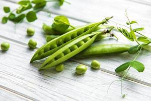 pois verts sur un fond en bois blanc. fond de nourriture saine. photo