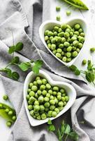 pois verts dans des bols en forme de coeur sur un fond de tissu photo