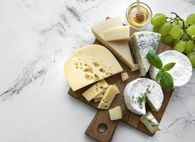 divers types de fromages, raisins et miel photo