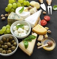 divers types de fromages, raisins, miel et collations photo