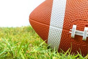 Ballon de football américain sur l'herbe verte isolé sur fond blanc photo