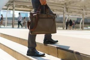 homme d'affaires marchant dans la ville et tenant une mallette photo