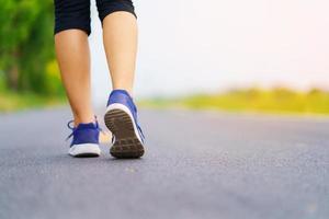 pieds de femme courant sur la route, formation de femme de forme physique saine photo