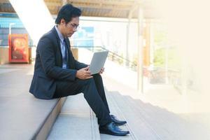 homme d'affaires assis sur les traces avec ordinateur portable photo
