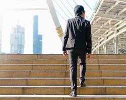 homme d'affaires marchant en plein air dans les pas de la rue dans la ville photo