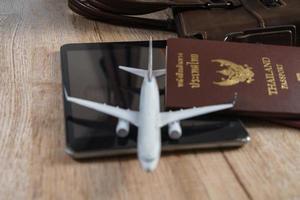 petit modèle d'avion, passeport thaïlandais sur fond de planche de bois photo