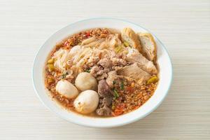 nouilles au porc et boulettes de viande dans une soupe épicée ou nouilles tom yum à l'asiatique photo