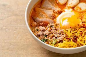 nouilles aux œufs avec porc et boulettes de viande dans une soupe épicée ou nouilles tom yum à l'asiatique photo