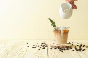 verser du lait dans un verre à café noir avec glaçon, cannelle et romarin sur fond de bois photo