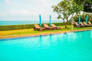 chaise piscine et parasol autour de la piscine avec fond de mer océan photo
