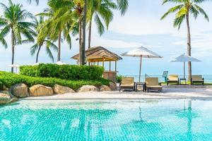 belle plage tropicale et mer avec parasol et chaise autour de la piscine de l'hôtel resort photo