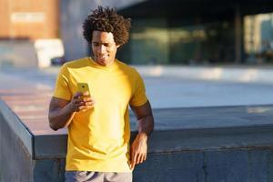 homme noir consultant son smartphone tout en se reposant de son entraînement. photo