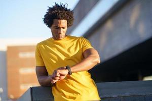 homme noir consultant sa smartwatch pour afficher ses données d'entraînement. photo