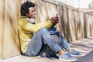 homme noir utilisant un smartphone posé sur le sol. photo