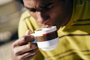 homme noir dégustant un café au café assis à table à l'extérieur photo