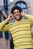 homme noir écoutant de la musique avec des écouteurs sans fil photo