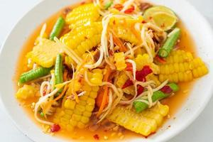 som tum - salade de papaye épicée thaï au maïs photo