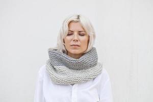 Jolie jeune femme en snood tricoté en laine grise chaude photo