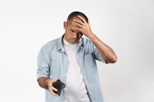 homme bouleversé tenant et regardant à l'intérieur de son portefeuille vide. pas d'argent. photo
