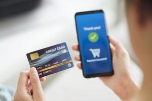 femme utilisant une carte de crédit et un téléphone intelligent pour les achats en ligne. photo