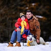 un père avec une fille chien husky se promène dans la forêt d'hiver. photo