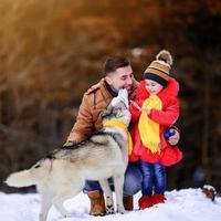 père avec fille et leur animal de compagnie dans le parc d'hiver, marchant avec un chien. photo