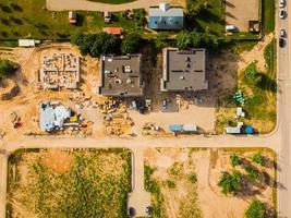 vue de haut en bas sur les toits de trois bâtiments en chantier dans un quartier résidentiel. concept de développement immobilier. photo