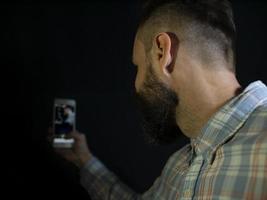 un homme avec une barbe et une moustache regarde dans le téléphone et fait un selfie photo