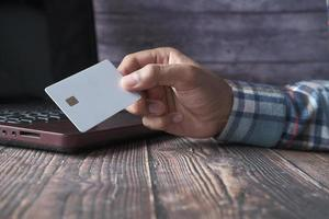 mains d'homme tenant une carte de crédit et utilisant un ordinateur portable pour acheter en ligne photo