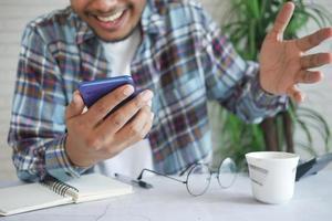 main de jeune homme heureux à l'aide de téléphone intelligent. photo