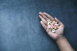 La main de l'homme avec un médicament renversé du contenant de la pilule photo
