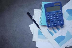 graphique financier, calculatrice et bloc-notes sur fond noir photo
