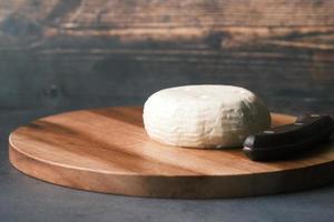 Fromage frais de forme ronde sur une planche à découper sur la table photo