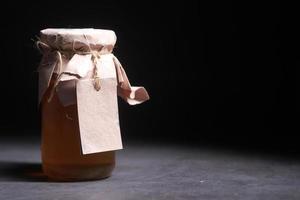 miel frais dans un bocal en verre avec une étiquette vide en papier photo