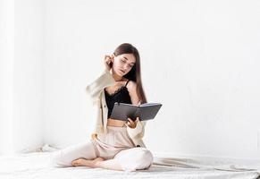 femme dans des vêtements confortables à la maison écrivant des notes assis sur le sol photo