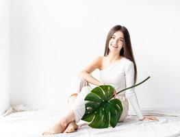 heureuse belle femme dans des vêtements confortables tenant une feuille verte de monstera photo