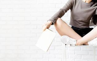 femme assise sur la chaise avec les jambes croisées en lisant un livre photo