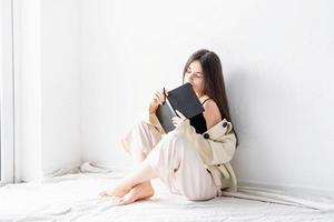 femme écrivant des notes assise sur le sol en train de rêver photo