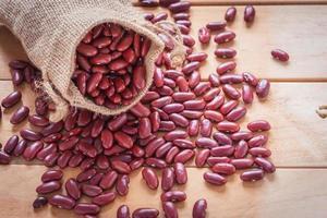 haricot rouge en sac sur fond en bois. alimentation saine avec des graines d'adzuki photo