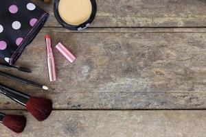 cosmétiques de maquillage et pinceaux sur fond de table en bois photo