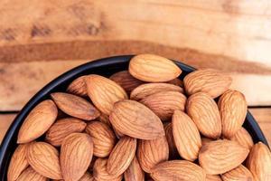 Close up raw graine d'amandes pelées dans un bol sur fond de bois photo