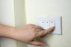 allumer la main humide allumer l'interrupteur électrique sur fond de mur blanc photo