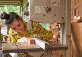 Les femmes debout sont du travail artisanal du bois coupé sur un banc de travail photo