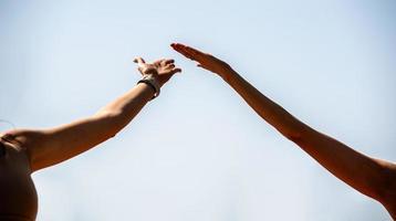 mains de personnes faisant du yoga sur la plage photo