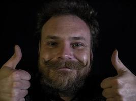 visage drôle d'un homme avec une barbe et une moustache et montrant les pouces vers le haut photo