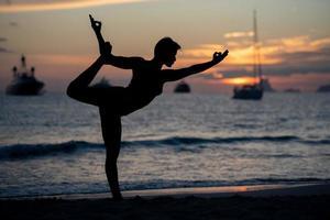 silhouette de modèle de remise en forme faisant du yoga au coucher du soleil photo