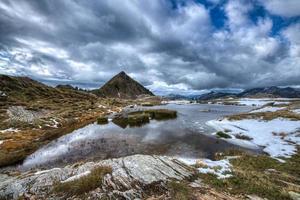 petit lac alpin avec la première neige sur les alpes italiennes photo