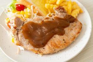 steak de porc avec sauce au poivre noir et mini salade photo