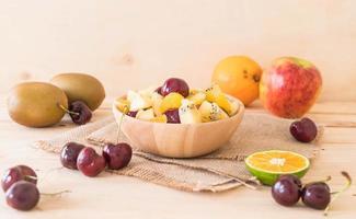 fruits tranchés mélangés dans un bol en bois photo