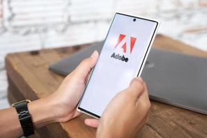 chiang mai, thaïlande 2021 -femme tenant un smartphone avec logo adobe sur l'écran photo